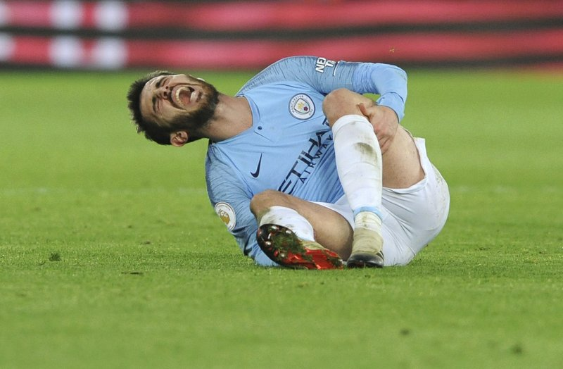 Manchester City's Bernardo Silva lies on the pitch in pain during the English Premier League soccer match between Leicester City and Manchester City at the King Power Stadium in Leicester, England, Wednesday, Dec. (AP Photo/Rui Vieira)