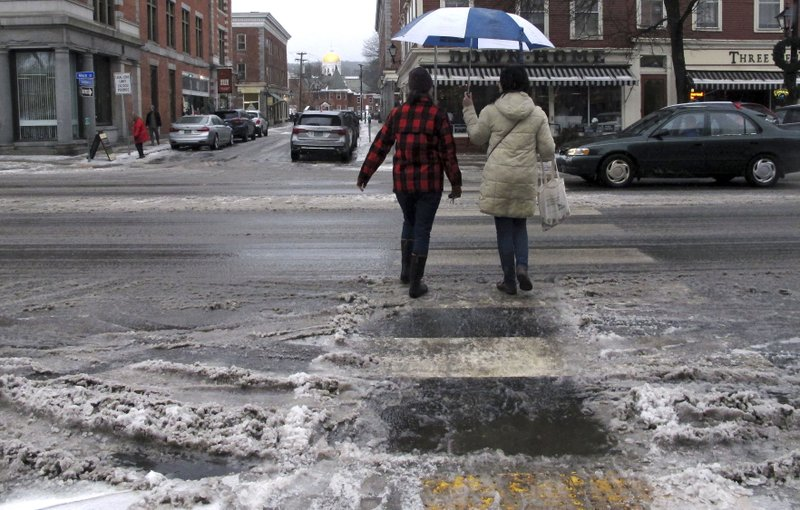 Pedestrians cross a slushy street in the rain on Friday, Dec. 28, 2018, in Montpelier, Vt. A winter storm brought snow, sleet, freezing rain and rain to northern New England, making for a dangerous and slippery commute. (AP Photo/Lisa Rathke)