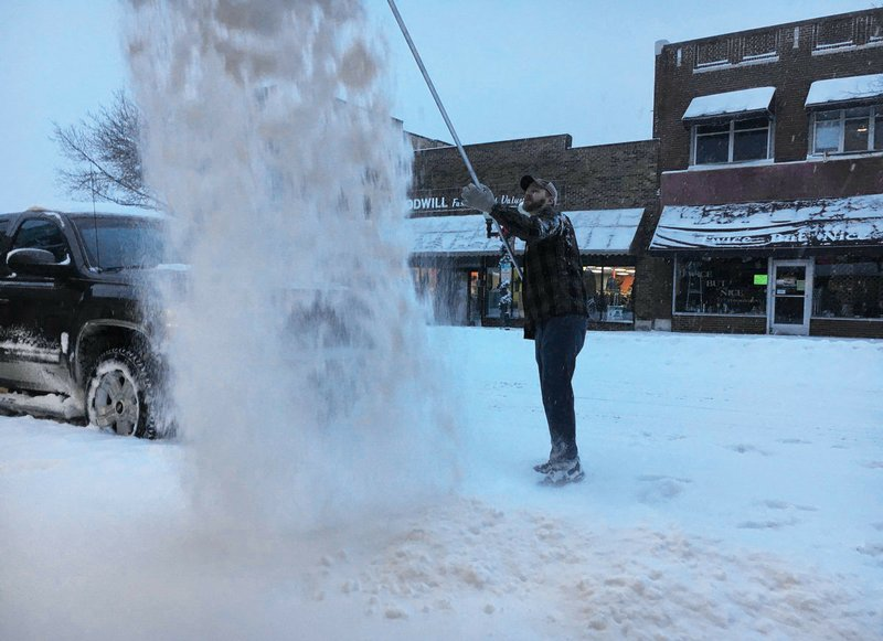 Tyler Winkka shovels the roof of the Fusion dance studio Thursday, Dec. 27, 2018, in Bemidji, Minn. Post-holiday travelers were finding driving difficult as a winter storm dumped heavy snow and whipped up gusty winds across parts of the Dakotas and Minnesota on Thursday. (John Enger/Minnesota Public Radio via AP)