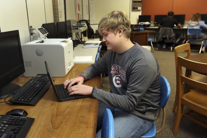 Braxton Moral, 16, sits in the computer room of Ulysses High School in Ulysses, Kan., on Wednesday, Dec. (Sandra J. Milburn/The Hutchinson News via AP)