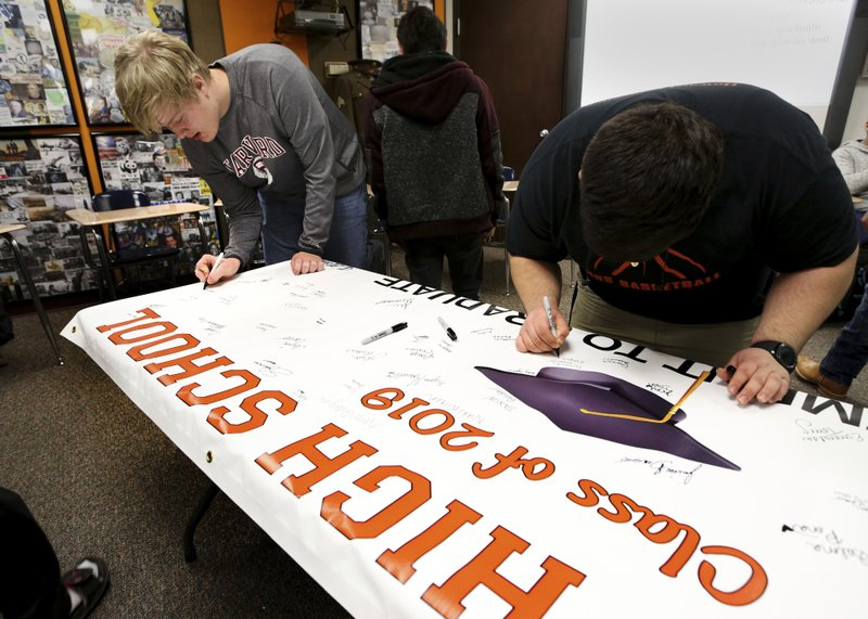 Braxton Moral, 16, left, signs the Class of 2019