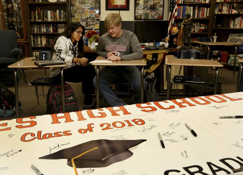 Government class students Alejandra Corral, left, and Braxton Moral work on calculating the estimated cost of living expenses as part of a talk about students who graduate high school making on average more money than non-graduates, at Ulysses High School in Ulysses, Kan. (Sandra J. Milburn/The Hutchinson News via AP)
