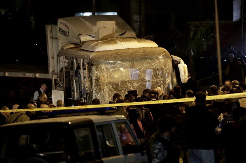 Security forces stand near a tourist bus after a roadside bomb in an area near the Giza Pyramids in Cairo, Egypt, Friday, Dec. (AP Photo/Nariman El-Mofty)