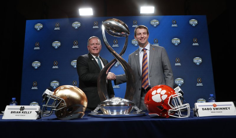 Notre Dame head coach Brian Kelly, left, and Clemson head coach Dabo Swinney shake hands and pose for photos after the NCAA Cotton Bowl football coaches' news conference in Dallas, Friday, Dec. (AP Photo/LM Otero)