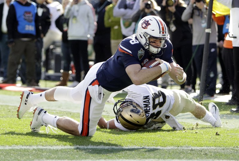 Auburn quarterback Jarrett Stidham (8) drives past Purdue safety Brennan Thieneman (38) and into the end zone in the first half of the Music City Bowl NCAA college football game Friday, Dec. (AP Photo/Mark Humphrey)