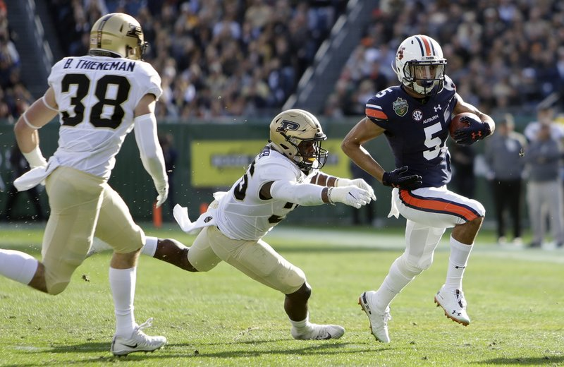 Auburn wide receiver Anthony Schwartz, right, runs past Purdue defenders Brennan Thieneman, left, and Jaylan Alexander, center, in the first half of the Music City Bowl NCAA college football game Friday, Dec. (AP Photo/Mark Humphrey)