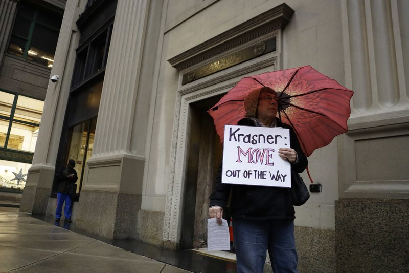A protestor holds a sign in support of Mumia Abu-Jamal outside the offices of District Attorney Larry Krasner, Friday, Dec. (AP Photo/Matt Slocum)