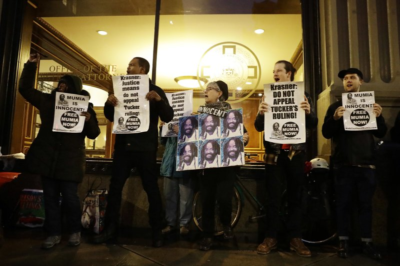 Demonstrators in support of Mumia Abu-Jamal stand outside the offices of District Attorney Larry Krasner, Friday, Dec. (AP Photo/Matt Slocum)