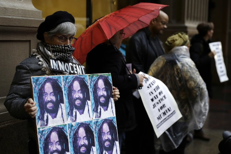 A protestor holds up a poster depicting Mumia Abu-Jamal during a demonstration outside the offices of District Attorney Larry Krasner, Friday, Dec. (AP Photo/Matt Slocum)