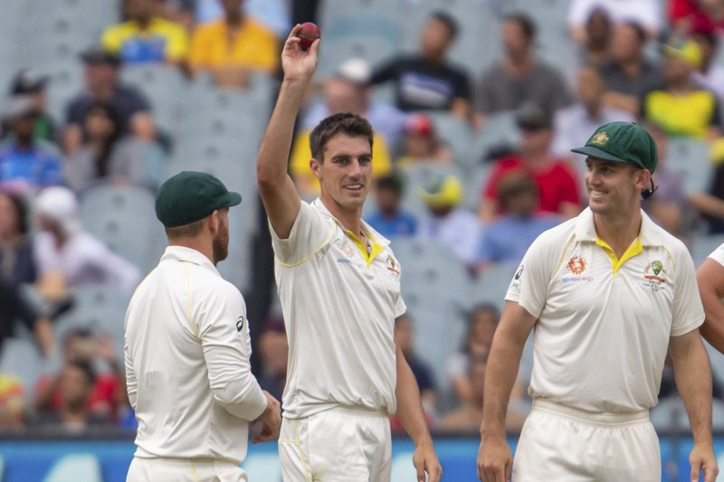 Australia's Pat Cummins, center, raises the ball after getting his 5th wicket in the 2nd innings during play on day four of the third cricket test between India and Australia in Melbourne, Australia, Saturday, Dec. (AP Photo/Asanka Brendon Ratnayake)
