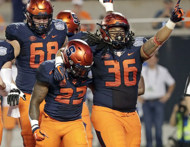 Syracuse fullback Chris Elmore (36) celebrates with running back Abdul Adams (23) after Adams scored a touchdown on a 3-yard run against West Virginia during the first half of the Camping World Bowl NCAA college football game Friday, Dec. (AP Photo/John Raoux)