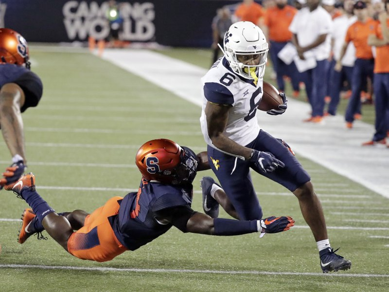West Virginia running back Kennedy McKoy (6) is tackled by Syracuse defensive back Evan Foster after gaining yardage during the first half of the Camping World Bowl NCAA college football game Friday, Dec. (AP Photo/John Raoux)