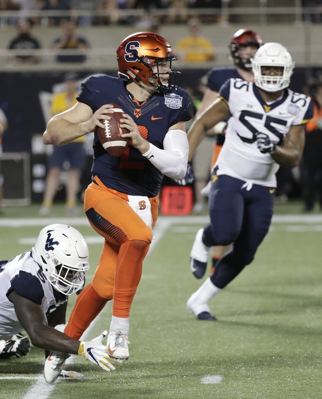 Syracuse quarterback Eric Dungey, center, scrambles as he is pressured by West Virginia defensive lineman Ezekiel Rose, left, and defensive lineman Dante Stills (55) during the first half of the Camping World Bowl NCAA college football game Friday, Dec. (AP Photo/John Raoux)
