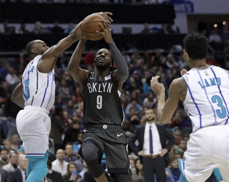 Brooklyn Nets' DeMarre Carroll (9) is fouled as he drives between Charlotte Hornets' Kemba Walker (15) and Jeremy Lamb (3) during the first half of an NBA basketball game in Charlotte, N. (AP Photo/Chuck Burton)