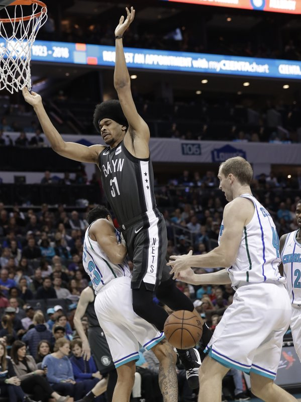 Brooklyn Nets' Jarrett Allen (31) loses the ball as he drives between Charlotte Hornets' Jeremy Lamb (3) and Cody Zeller during the first half of an NBA basketball game in Charlotte, N. (AP Photo/Chuck Burton)