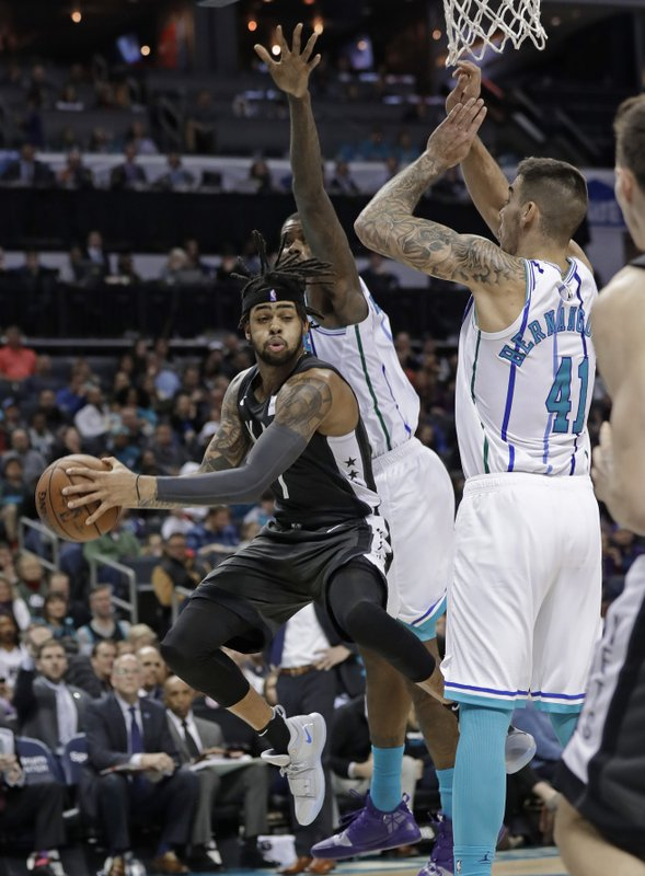 Brooklyn Nets' D'Angelo Russell (1) drives between Charlotte Hornets' Willy Hernangomez (41) and Marvin Williams during the first half of an NBA basketball game in Charlotte, N. (AP Photo/Chuck Burton)