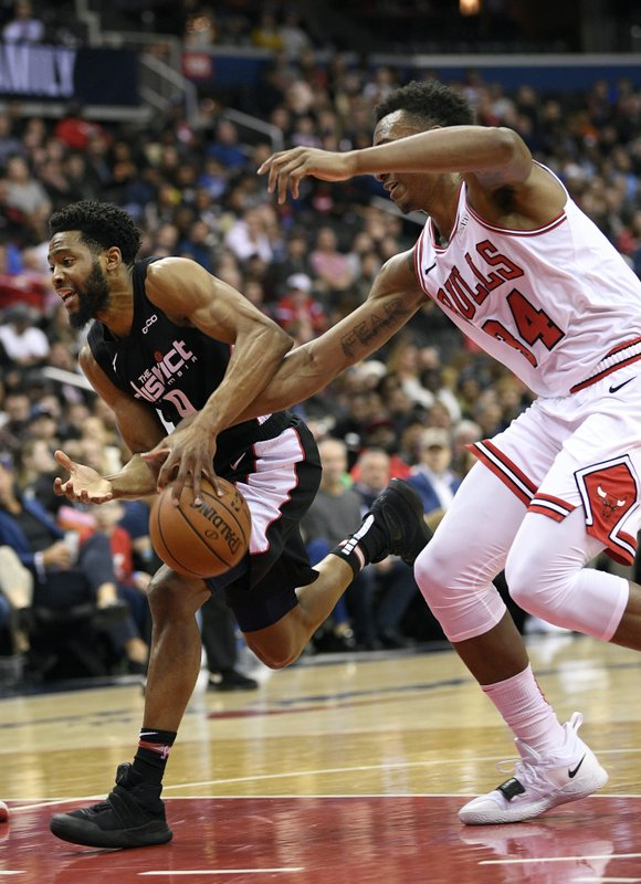 Chicago Bulls forward Wendell Carter Jr. (34) reaches for the ball against Washington Wizards guard Chasson Randle (9) during the first half of an NBA basketball game, Friday, Dec. (AP Photo/Nick Wass)