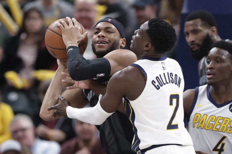 Indiana Pacers guard Darren Collison (2) ties up Detroit Pistons guard Bruce Brown (6) during the second half of an NBA basketball game in Indianapolis, Friday, Dec. (AP Photo/Michael Conroy)