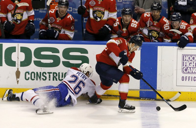 Florida Panthers right wing Evgenii Dadonov, right, tries to elude Montreal Canadiens defenseman Jeff Petry (26) in the second period of an NHL hockey game, Friday, Dec. (AP Photo/Joe Skipper)