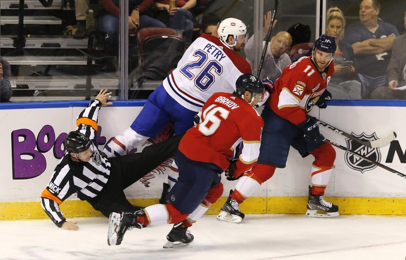 Referee Gord Dwyer, left, goes to the ice after being caught between Montreal Canadiens defenseman Jeff Petry (26) and Florida Panthers center Aleksander Barkov (16) in the first period of an NHL hockey game, Friday, Dec. (AP Photo/Joe Skipper)