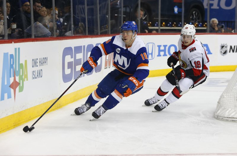 New York Islanders left wing Anthony Beauvillier (18) plays the puck against Ottawa Senators left wing Ryan Dzingel (18) during the second period of an NHL hockey game, Friday, Dec. (AP Photo/Noah K. Murray)