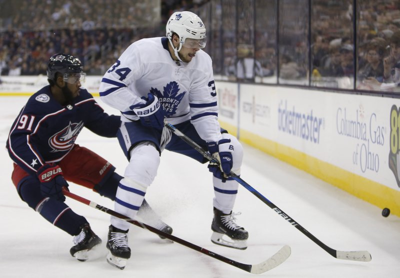 Toronto Maple Leafs' Auston Matthews, right, keeps the puck away from Columbus Blue Jackets' Anthony Duclair during the first period of an NHL hockey game Friday, Dec. (AP Photo/Jay LaPrete)