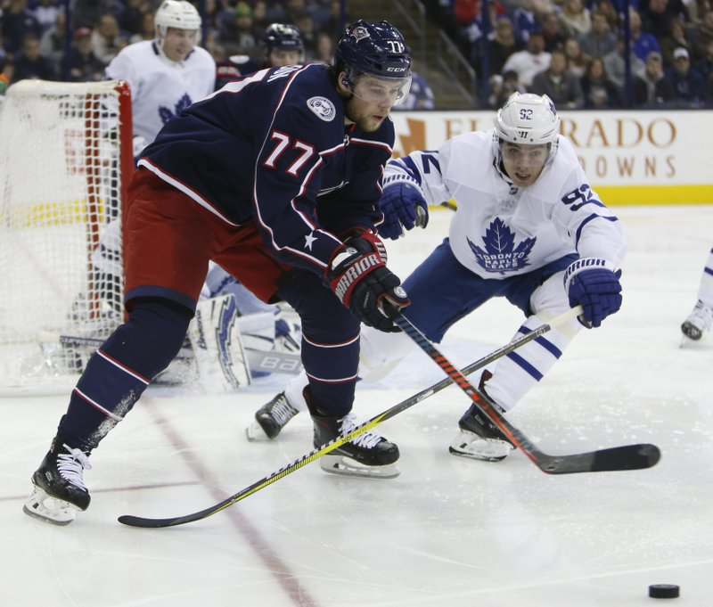 Columbus Blue Jackets' Josh Anderson, left, looks for an open pass as Toronto Maple Leafs' Igor Ozhiganov, of Russia, defends during the second period of an NHL hockey game Friday, Dec. (AP Photo/Jay LaPrete)
