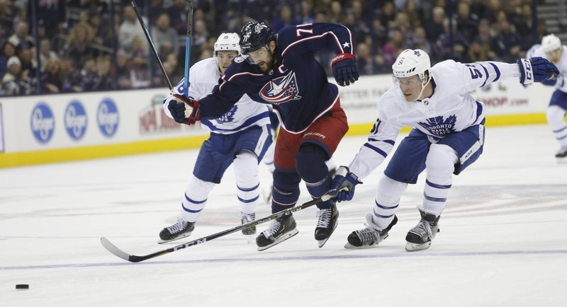 Columbus Blue Jackets' Nick Foligno, center, carries the puck across the blue line between Toronto Maple Leafs' Andreas Johnsson, left, of Sweden, and Jake Gardiner during the second period of an NHL hockey game Friday, Dec. (AP Photo/Jay LaPrete)