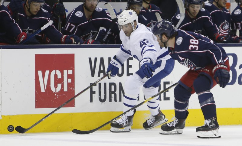 Toronto Maple Leafs' Trevor Moore, left, carries the puck up ice as Columbus Blue Jackets' Boone Jenner defends during the first period of an NHL hockey game Friday, Dec. (AP Photo/Jay LaPrete)