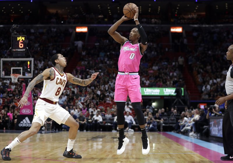 Miami Heat guard Josh Richardson (0) attempts a three-point basket over Cleveland Cavaliers guard Jordan Clarkson (8) during the first half of an NBA basketball game, Friday, Dec. (AP Photo/Lynne Sladky)