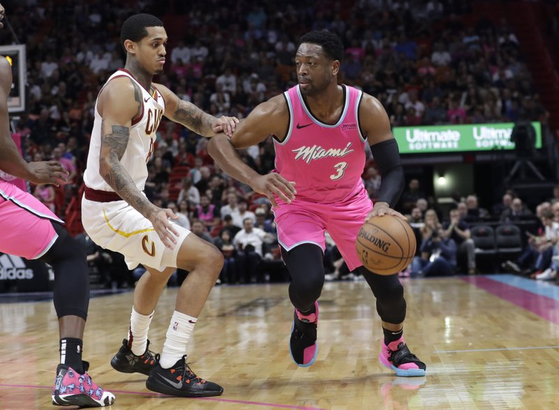 Miami Heat guard Dwyane Wade (3) handles the ball as Cleveland Cavaliers guard Jordan Clarkson defends during the first half of an NBA basketball game, Friday, Dec. (AP Photo/Lynne Sladky)