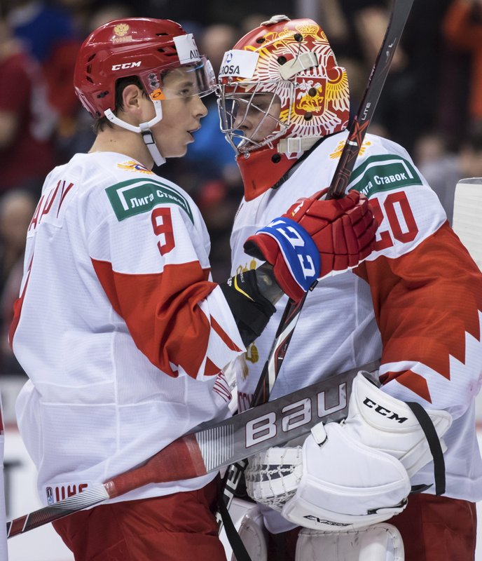 Russia's Artyom Galimov, left, and goalie Pyotr Kochetkov celebrate their win over the Czech Republic in IIHF world junior hockey championship game action in Vancouver, British Columbia, Friday, Dec. (Darryl Dyck/The Canadian Press via AP)