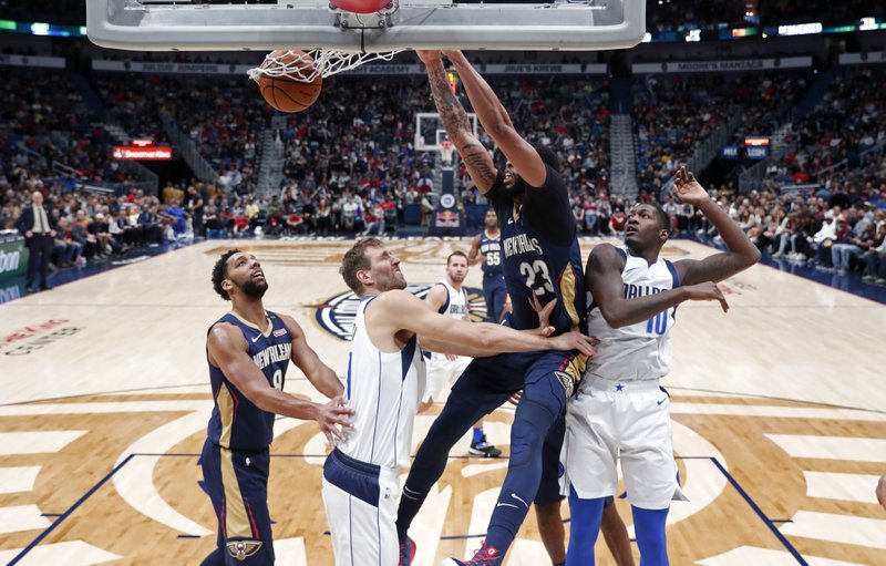 New Orleans Pelicans forward Anthony Davis (23) dunks over Dallas Mavericks forwards Dorian Finney-Smith (10) and Dirk Nowitzki during the first half of an NBA basketball game in New Orleans, Friday, Dec. (AP Photo/Gerald Herbert)