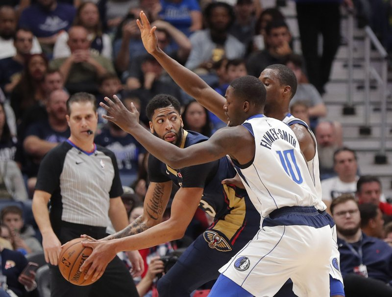 New Orleans Pelicans forward Anthony Davis looks to pass the ball past Dallas Mavericks forward Dorian Finney-Smith (10) during the first half of an NBA basketball game in New Orleans, Friday, Dec. (AP Photo/Gerald Herbert)