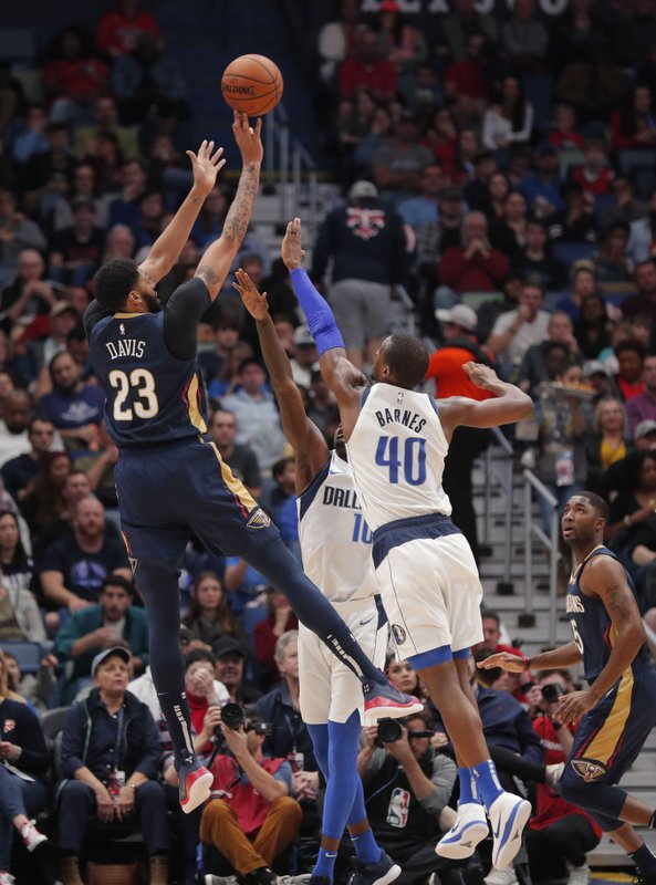 New Orleans Pelicans forward Anthony Davis (23) shoots as Dallas Mavericks forwards Dorian Finney-Smith (10) and Harrison Barnes (40) defend during the first half of an NBA basketball game in New Orleans, Friday, Dec. (AP Photo/Gerald Herbert)