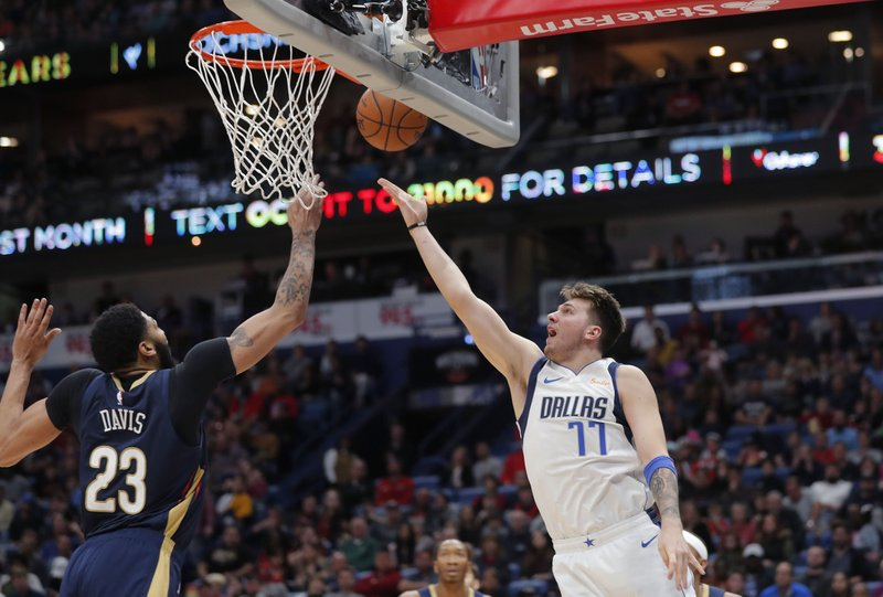 Dallas Mavericks forward Luka Doncic (77) goes to the basket against New Orleans Pelicans forward Anthony Davis (23) during the first half of an NBA basketball game in New Orleans, Friday, Dec. (AP Photo/Gerald Herbert)