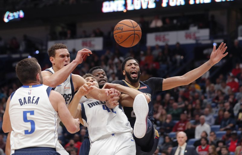 New Orleans Pelicans forward Anthony Davis, right, and Dallas Mavericks forward Maximilian Kleber (42), forward Dwight Powell and guard J. (5) compete for a rebound during the second half of an NBA basketball game in New Orleans, Friday, Dec. 28, 2018. The Pelicans won 114-112. (AP Photo/Gerald Herbert)