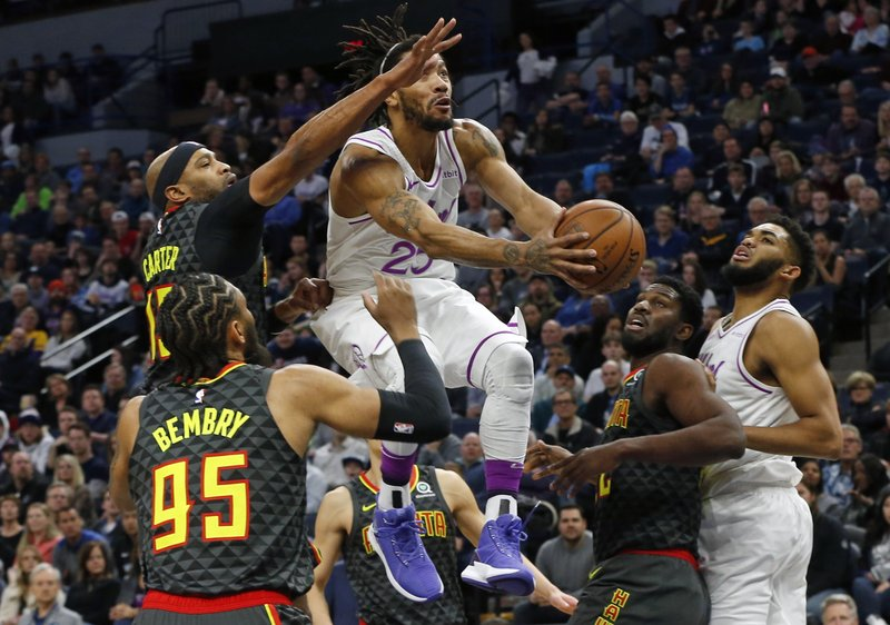 Minnesota Timberwolves' Derrick Rose, center, drives between Atlanta Hawks' Vince Carter, top left, and other defenders during the first half of an NBA basketball game Friday, Dec. (AP Photo/Jim Mone)