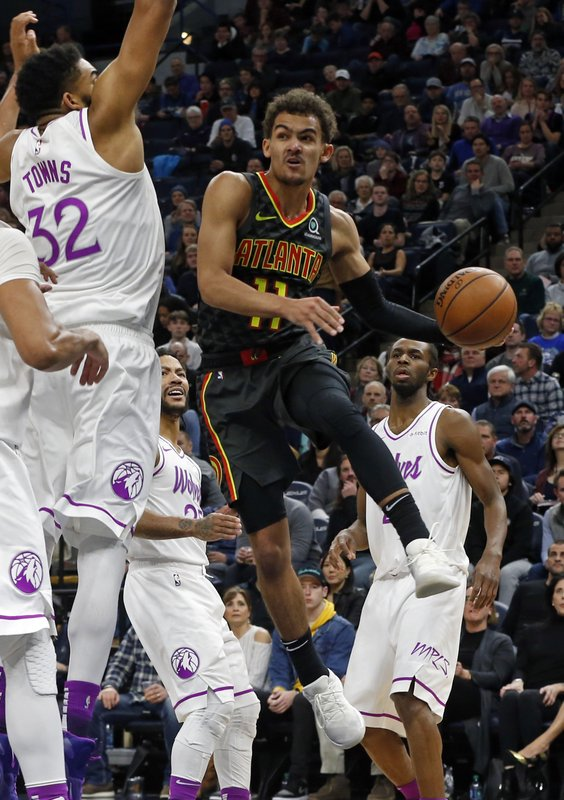 Atlanta Hawks' Trae Young, right, goes to the air to make a pass as Minnesota Timberwolves' Karl-Anthony Towns defends during the second half of an NBA basketball game Friday, Dec. (AP Photo/Jim Mone)