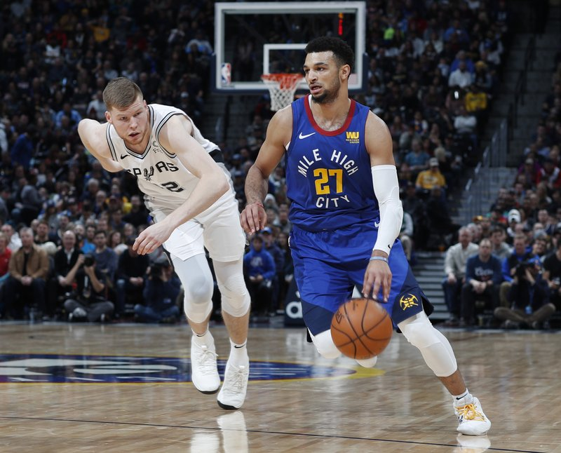 Denver Nuggets guard Jamal Murray, right, drives to the net past San Antonio Spurs forward Davis Bertans in the first half of an NBA basketball game Friday, Dec. (AP Photo/David Zalubowski)