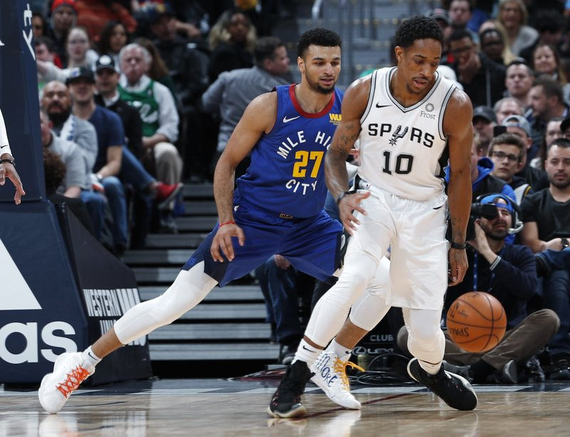 San Antonio Spurs guard DeMar DeRozan, front, pursues the ball with Denver Nuggets guard Jamal Murray in the first half of an NBA basketball gsm Friday, Dec. (AP Photo/David Zalubowski)