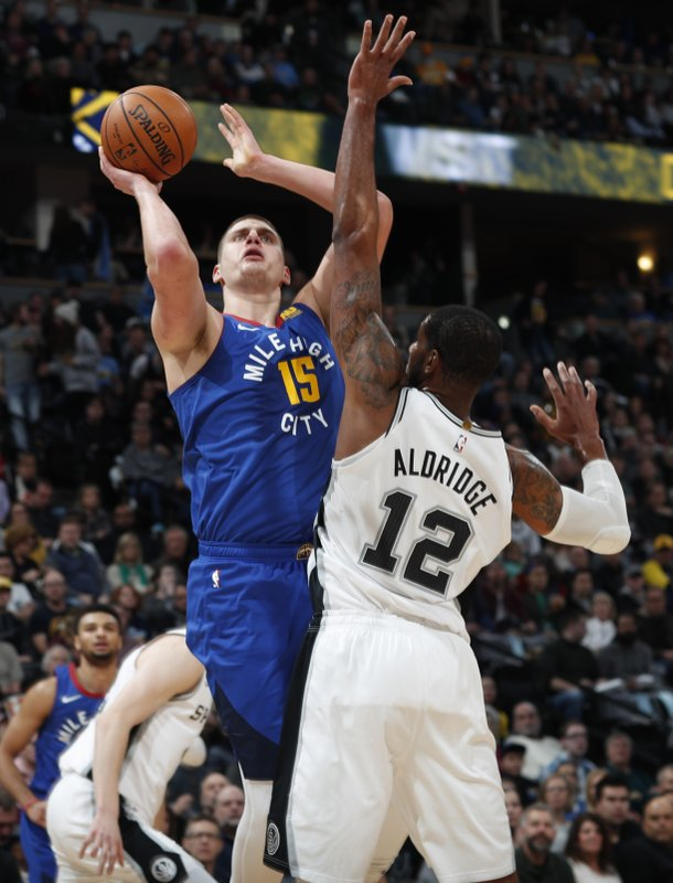 Denver Nuggets center Nikola Jokic, back, goes up for a basket over San Antonio Spurs forward LaMarcus Aldridge in the first half of an NBA basketball gsm Friday, Dec. (AP Photo/David Zalubowski)
