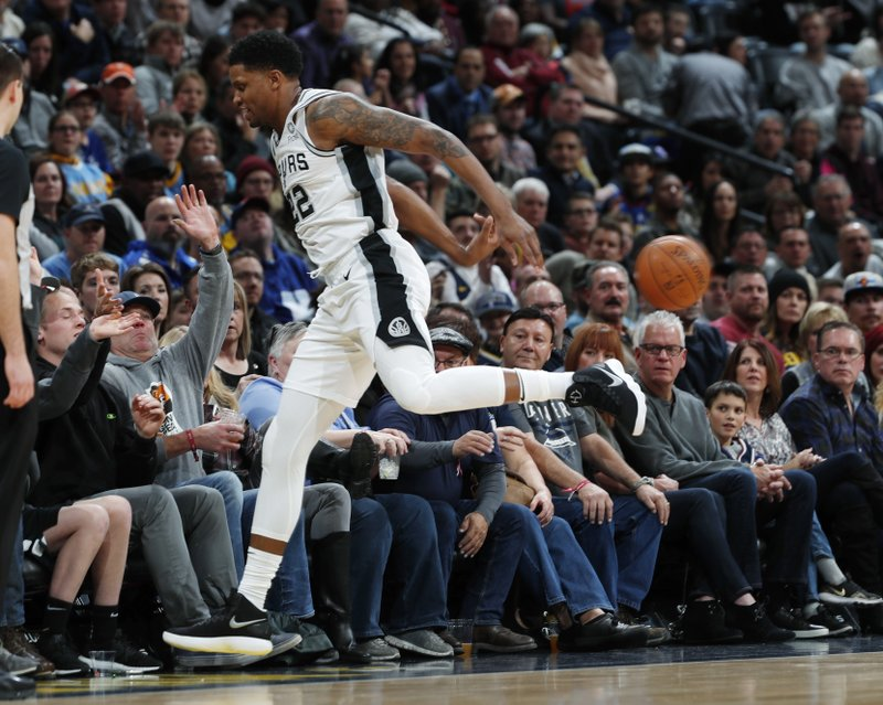 San Antonio Spurs forward Rudy Gay saves the ball from bouncing out of play as he runs into fans in the courtside seats in the first half of an NBA basketball game against the Denver Nuggets, Friday, Dec. (AP Photo/David Zalubowski)