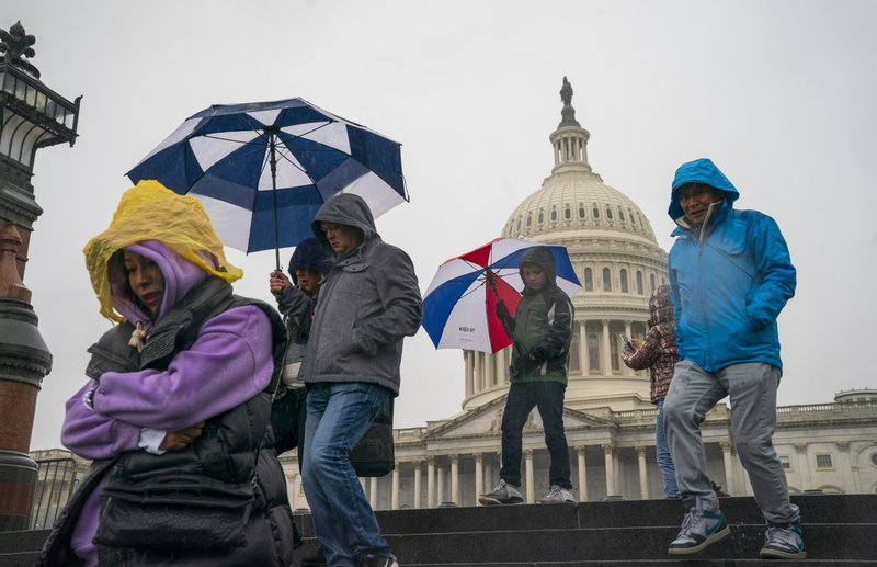 Tourists arrive to visit the U.S. Capitol on a rainy morning in Washington, Friday, Dec. 28, 2018, during a partial government shutdown. (AP Photo/J. Scott Applewhite)