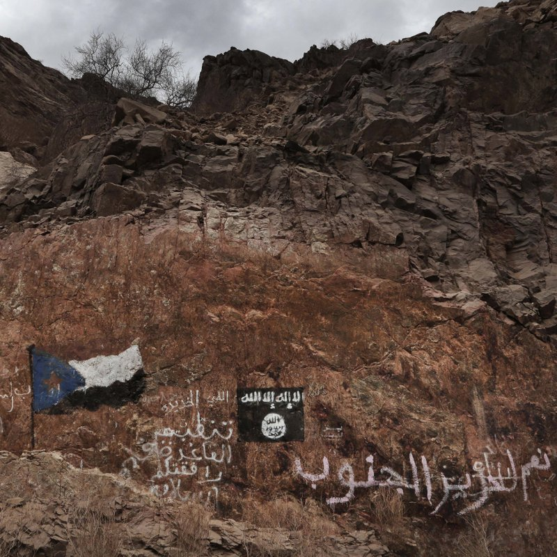 This July 24, 2018 photo shows the al-Qaida flag painted on rocks near the southern flag with Arabic that reads,
