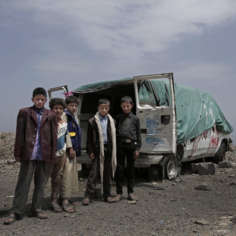 Boys stand next to the dilapidated remains of a van with four flat tires half-sunk in the dirt on a mountain in Ibb, Yemen on Aug. (AP Photo/Nariman El-Mofty)