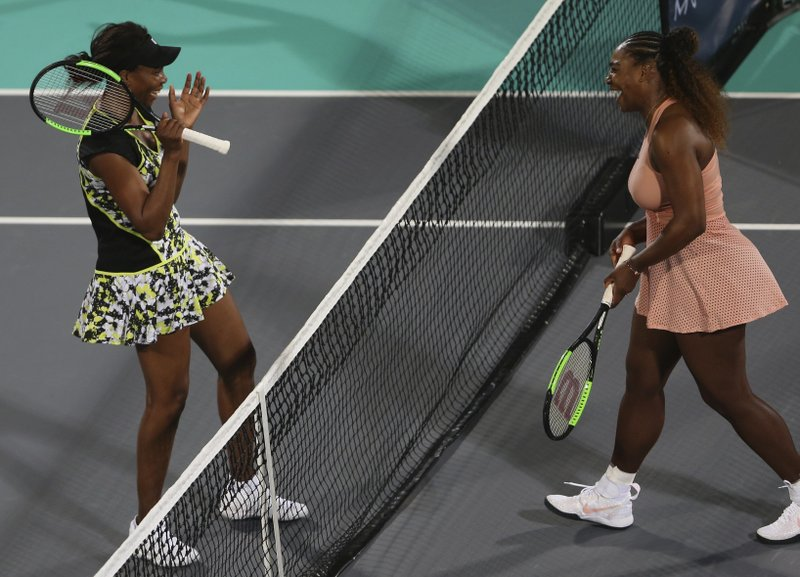 Venus Williams, left, from the U.S., celebrates after defeating her sister, Serena, in a match during the opening day of the Mubadala World Tennis Championship in Abu Dhabi, United Arab Emirates, Thursday, Dec. (AP Photo/Kamran Jebreili)