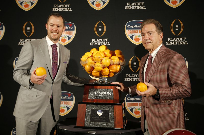 Alabama head coach Nick Saban, right, stands with Oklahoma head coach Lincoln Riley at an NCAA college football news conference in Fort Lauderdale, Fla. (AP Photo/Joe Skipper)