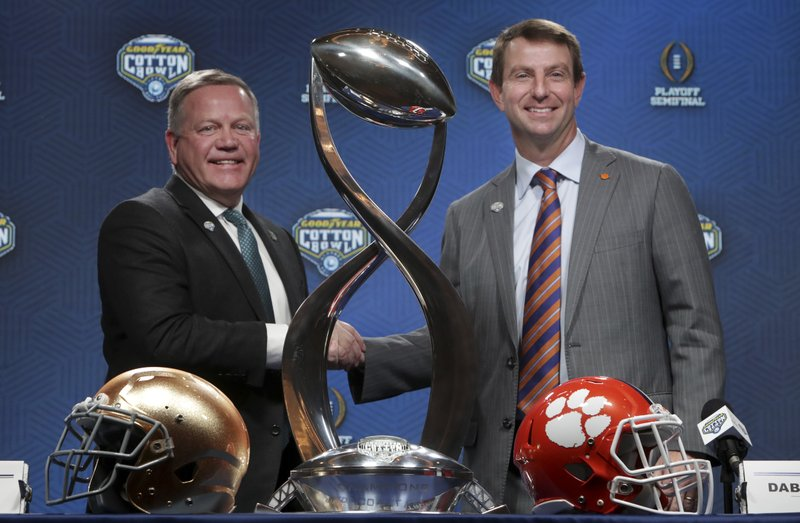 Notre Dame head coach Brian Kelly, left, and Clemson head coach Dabo Swinney share a moment during the NCAA Cotton Bowl football coaches' news conference in Dallas, Friday, Dec. (AP Photo/LM Otero)