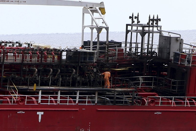 A man on the deck following a fire aboard the Athlos tanker, as it lays aground about 200-yards from the village of Zygi off the south coast of Cyprus, Saturday, Dec. (AP Photo/Petros Karadjias)